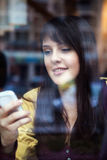 Beautiful young girl using smart phone in a cafe Stock Photos