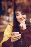 Beautiful young girl using smart phone in a cafe Stock Image
