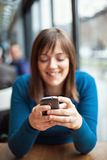 Beautiful young girl using smart phone in a cafe Royalty Free Stock Photos
