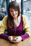 Beautiful young girl using smart phone in a cafe Royalty Free Stock Photo