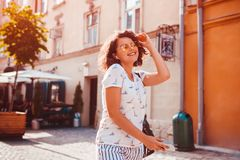 Beautiful young girl using smartphone and listening to the music walking on street. Woman dancing and singing. Beautiful young girl using smartphone and stock photo