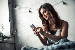 Girl in bed. Beautiful young girl is using a smartphone and smiling while sitting in bed at home Royalty Free Stock Photos