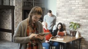 Young girl using tablet. Beautiful young girl is using tablet standing in the co-working space. Professional team of co-workers are talking and discussing some stock footage