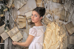 Beautiful young girl in a vintage dress. Beautiful young girl in a vintage dress with wings on her back stock image