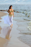 Beautiful young girl walking on beach Royalty Free Stock Images