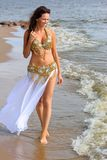 Beautiful young girl walking on beach Royalty Free Stock Image