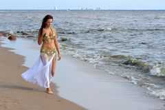 Beautiful young girl walking on beach Stock Photo