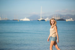 Beautiful young girl walking on the beach Stock Images