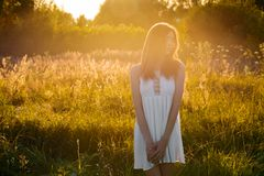 Beautiful young girl walking in the evening outdoors. In field stock photo