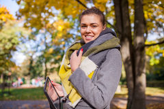 Beautiful young girl walking in park with tablet pc. Autumn time Royalty Free Stock Photography