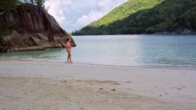 Beautiful young girl walks the beach in the lagoon on the Seychelles. stock video footage