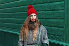 Beautiful young girl in warm clothes and knit cap stands near a Royalty Free Stock Photos