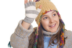 Beautiful young girl in warm winter clothes smiles and waving Royalty Free Stock Images