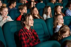 Youth watching film and laughing in cinema. Beautiful young girl watching film with steadfast eyes and smiling, expressing facial emotions. Youth having fun royalty free stock image