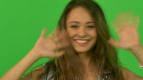 Beautiful young girl waving at the camera. Close stock footage