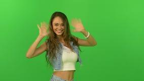 Beautiful young girl waving at the camera stock video