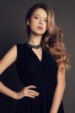 Beautiful young girl wearing black dress with bijou. Fashion studio photo of beautiful young girl with dark natural hair wearing black dress and bijou Royalty Free Stock Image