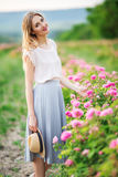 Beautiful young girl is wearing casual clothes sitting in a garden with pink blossom roses Royalty Free Stock Images