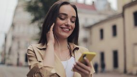 Beautiful Young Girl Wearing Headphones Enjoy Listening to Music Using her Smartphone and Smiling Walking at City. Background Close Up stock footage