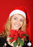 Beautiful young girl wearing Santa hat. And holding a red Poinsettia over red background Stock Photos