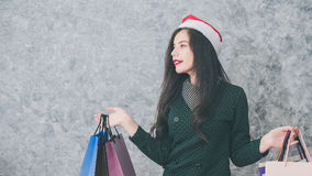 Beautiful young girl wearing a Santa hat holding lots of shopping bags Stock Photos