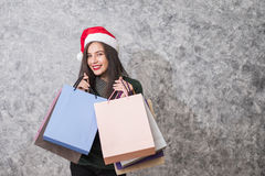Beautiful young girl wearing a Santa hat holding lots of shopping bags Royalty Free Stock Photos