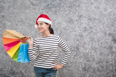 Beautiful young girl wearing a Santa hat holding lots of shopping bags Royalty Free Stock Image
