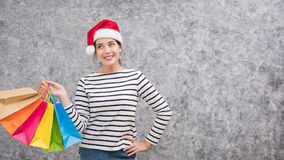 Beautiful young girl wearing a Santa hat holding lots of shopping bags Stock Photography