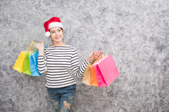 Beautiful young girl wearing a Santa hat holding lots of shopping bags Royalty Free Stock Images