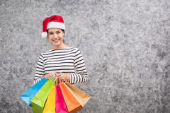Beautiful young girl wearing a Santa hat holding lots of shopping bags Royalty Free Stock Photo