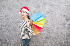 Beautiful young girl wearing a Santa hat holding lots of shopping bags Stock Images