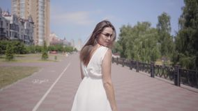 Glamorous young girl wearing sunglasses and a long white summer fashion dress walking outdoors. Leisure of a pretty stock footage