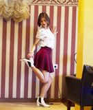 Beautiful young girl wearing a white t-shirt and red skirt, white shoes. Posing in the photo studio on the background stock images
