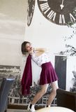 Posing in the photo studio on the background that can be seen in the Petrovaradin Clock. Beautiful young girl wearing a white t-shirt and red skirt, white shoes stock photo
