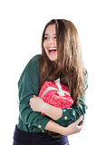 Beautiful young girl on a white background holding a box with a gift. Smiles. Stock Images