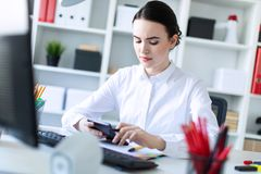 A young girl in the office holds a pen in her hand and works with a calculator, documents and a computer. Beautiful young girl in a white blouse and black skirt Stock Photo