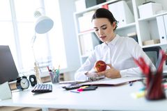 Young girl in the office working with documents and holding an apple. Beautiful young girl in a white blouse and black skirt. Girl with dark hair and beautiful Stock Images