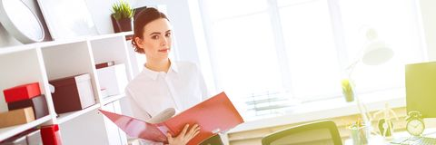 Young girl in the office near the rack and scrolls through the folder with the documents. Beautiful young girl in a white blouse and black skirt. Girl with dark royalty free stock image