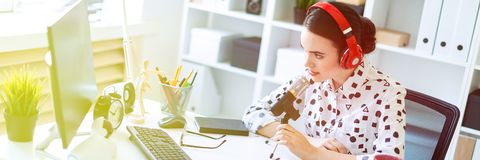 Beautiful young girl is sitting in headphones and with a microphone at the desk in the office. royalty free stock photos
