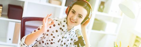 A beautiful young girl sits in headphones and with a microphone at the desk in the office and shows a sign of okay. Beautiful young girl in a white blouse in a royalty free stock images