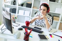 Beautiful young girl sitting in headphones at desk in office, eating yogurt and looking at monitor. Beautiful young girl in a white blouse in a geometric Royalty Free Stock Image
