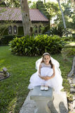 Beautiful young girl in white dress on bench Stock Photos