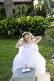 Beautiful young girl in white dress on bench Stock Photography