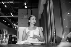 Beautiful young girl in white dress with white cup of coffee is sitting in the urban vintage cafe and tenderness looking afar stock photography