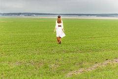 Beautiful young girl in a white dress with long hair on the field on a cloudy day royalty free stock photography