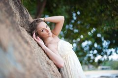 A beautiful young girl in white dress resting in s Stock Image