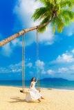 Beautiful young girl in a white dress sits on a swing under a pa Stock Photos