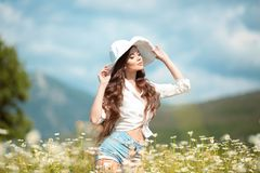 Beautiful young girl in white hat over chamomile field. Carefree happy brunette woman with healthy wavy hair having fun outdoor in stock images