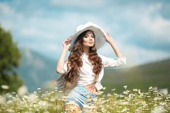 Beautiful young girl in white hat over chamomile field. Carefree happy brunette woman with healthy wavy hair having fun outdoor in stock photography
