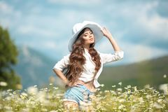 Beautiful young girl in white hat over chamomile field. Carefree happy brunette woman with healthy wavy hair having fun outdoor in royalty free stock photography